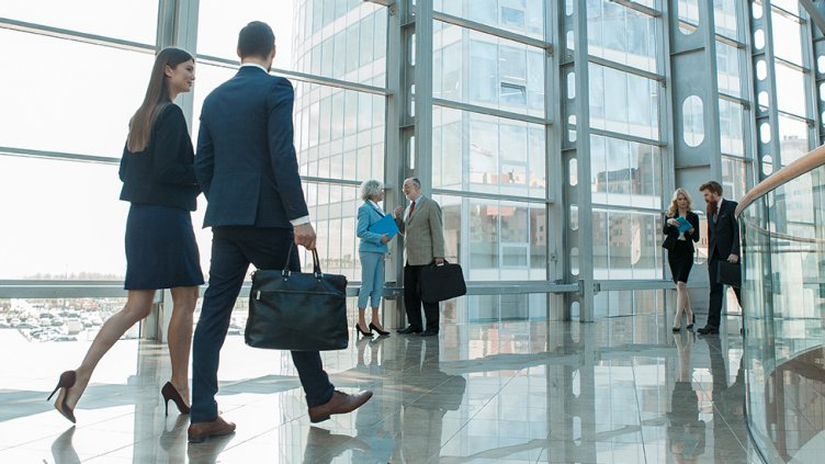 business man and woman walk down hallway in modern building