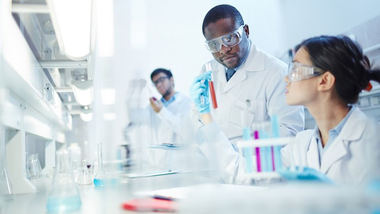 Latin-American scientist in background to scientists performing lab experiments